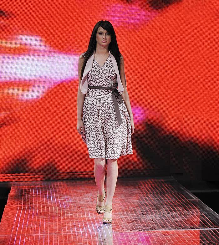 Model walking down a runway at fashion show.