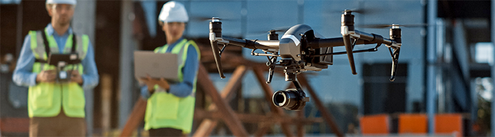 Several people on a job site using a drone to survey the field.