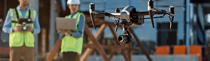 Several people on a job site using a streaming-enabled drone to survey.