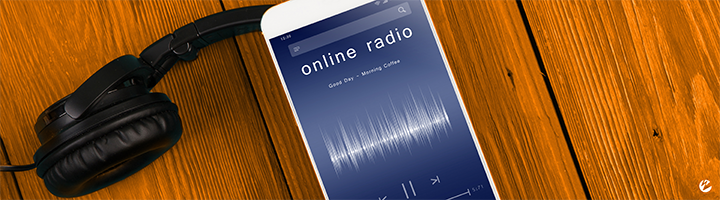 A mobile phone with a live online radio stream playing and headphones.