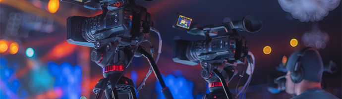 A video production team live streaming a festival by capturing the live event on camera.