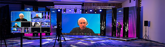 A live event broadcast with a man on a large screen presenting on a topic and several monitors around playing the same broadcast.