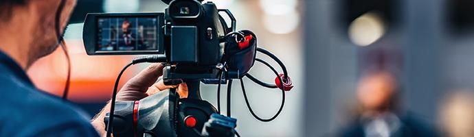Cameraman shooting a live stream of a man behind a desk.