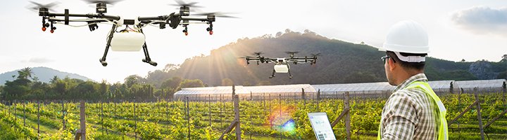 An agriculture professionals using video-enabled drones as a smart surveillance solution for surveying crop yields.