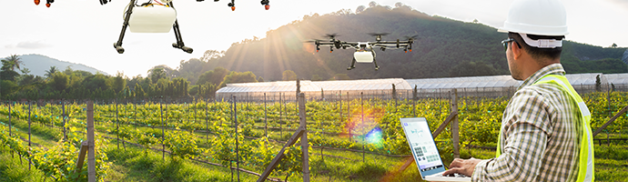 An agriculture professional operating a streaming-enabled drone for crop surveillance.