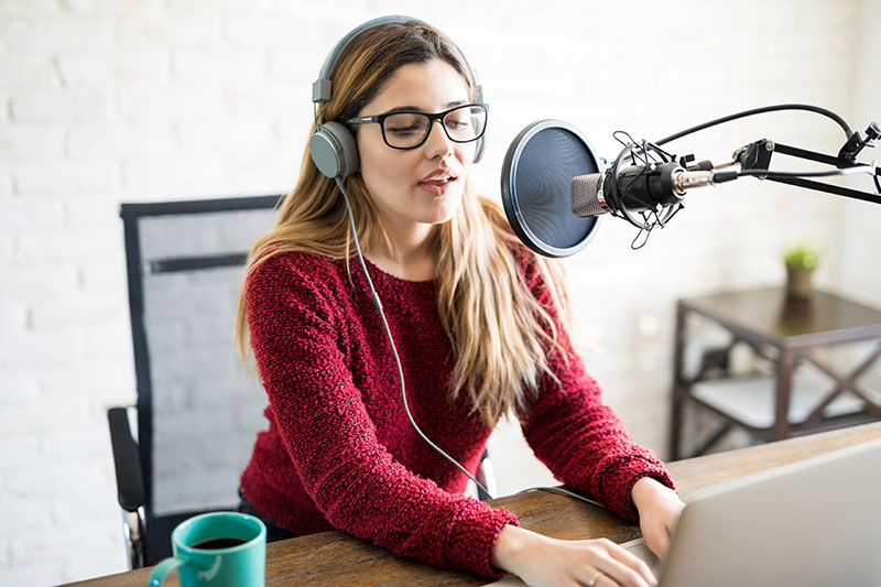 A woman radio host wearing headphones and broadcasting a live stream audio-only.