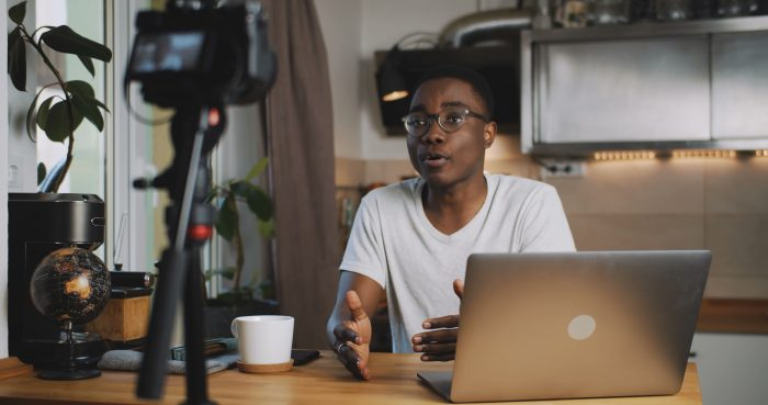 Professional at-home live stream set up with a man in front of camera and laptop.