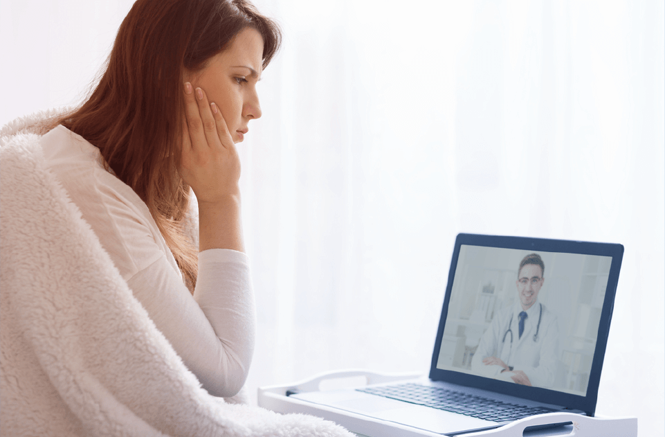 Woman consulting with remote doctor over live stream telehealth appointment on laptop.